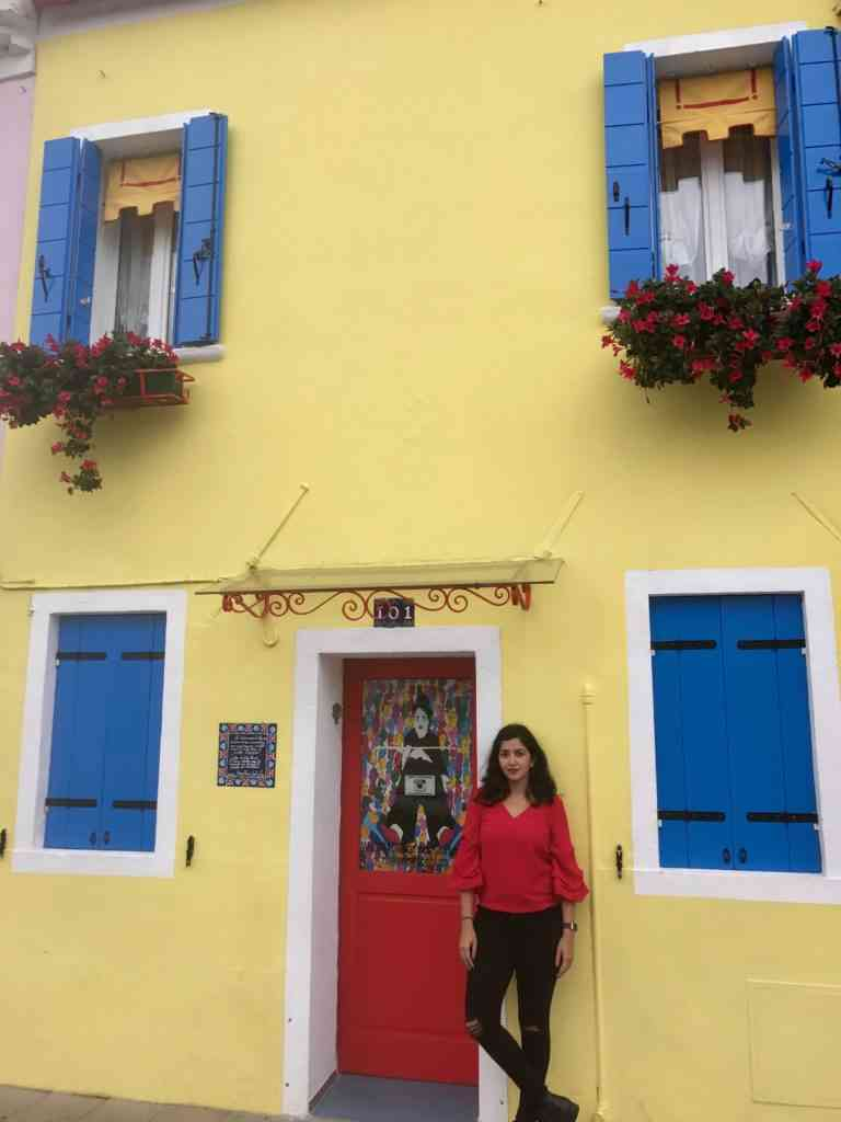 Standing by an awesome colorful building in Burano