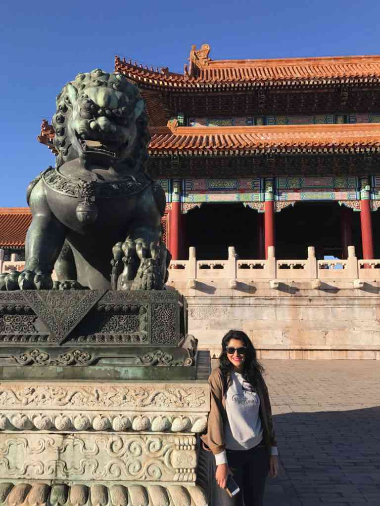 Natasha in front of a lion statue at The Palace Museum in Beijing