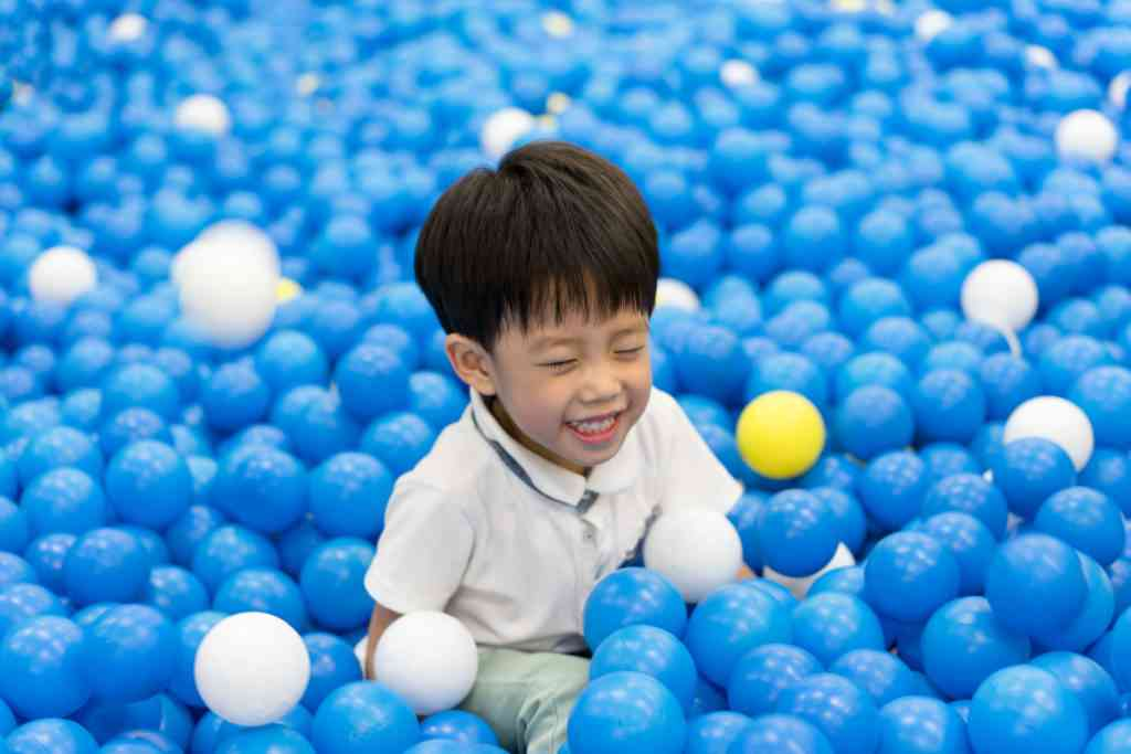 young boy in blue ball pit