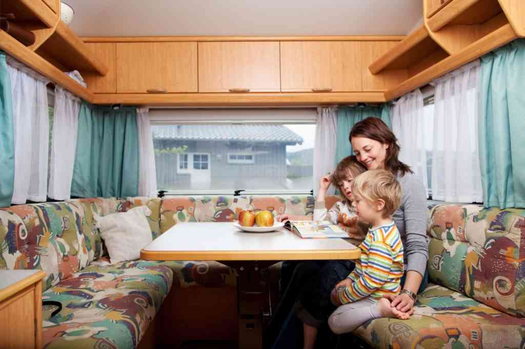 mid adult woman with sons reading story book at table in caravan for travel with kids quotes