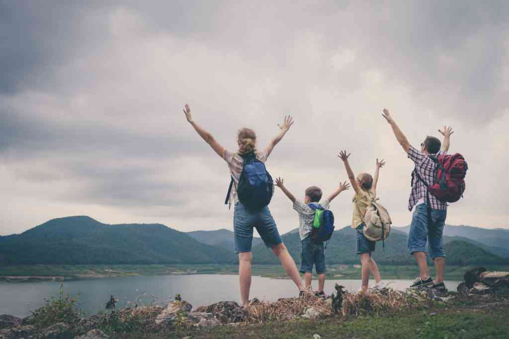 Happy family standing near the lake at the day time.  Concept of friendly family. travel with kids quotes
