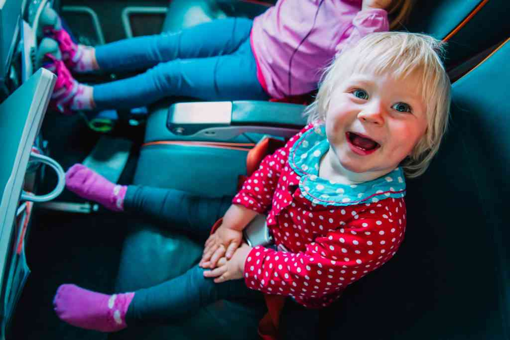 happy cute little baby girl with her sister travel by plane, family in flight
