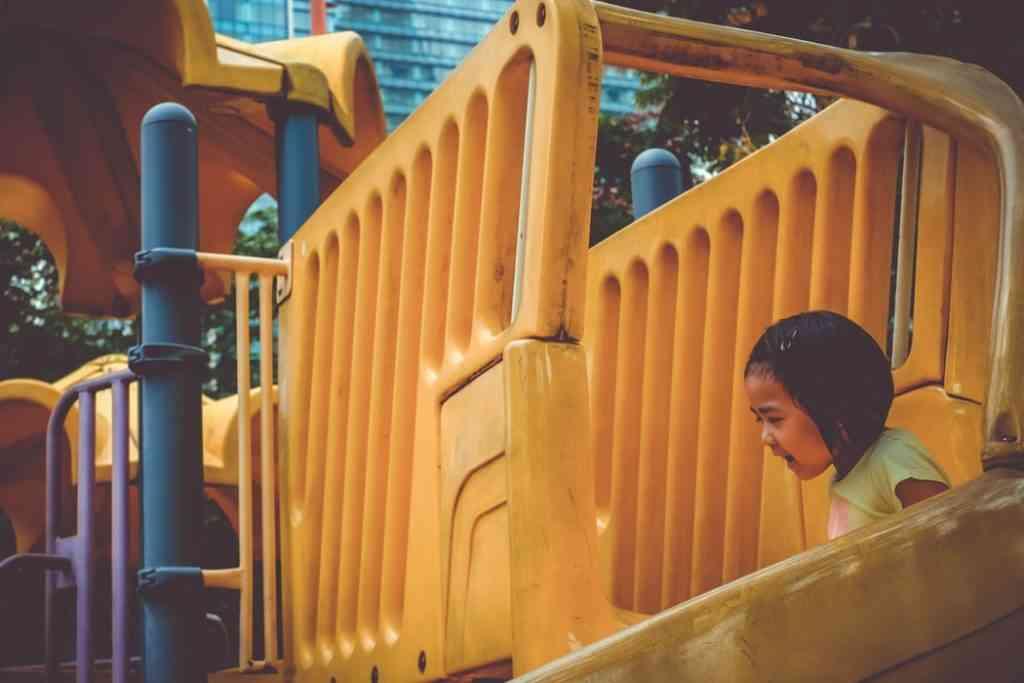 girl playing on playground slide