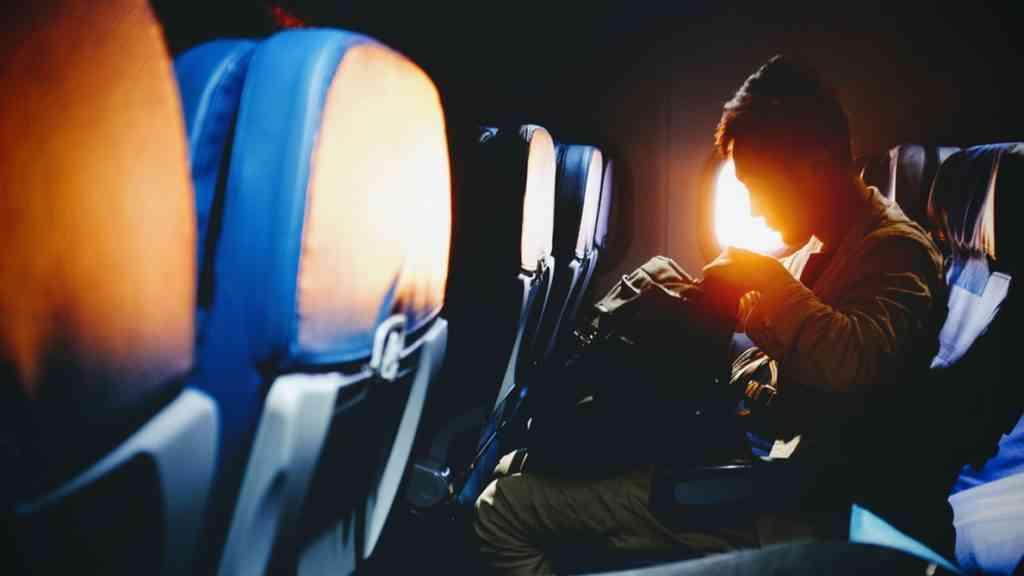 man holding bag on airplane